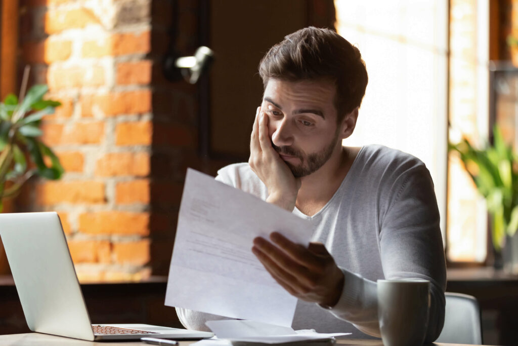 Man reading bill looking concerned